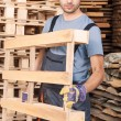 Warehouse worker moving wood pallets — Stock Photo #21137253