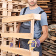 Warehouse worker moving wood pallets — Stock Photo