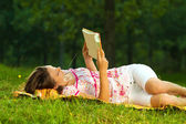 Beautiful young brunette reading on a meadow in the park — Stock Photo