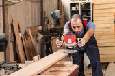 Carpenter with an electric router — Stock Photo