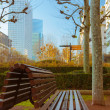 Vacant bench in a business area with skyscrapers and blue sky in — Stock Photo