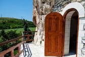 Orthodox monastery excavated in the rocks with open wooden door — Stock Photo