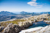 A small lake with snow and view towards mountains and the sea in — Stock Photo