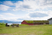 Houses with grass covered roofs and benches near a fjord — Stock Photo