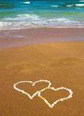 Connected hearts on beach - love concept — Stock Photo