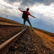 Teen girl with problems walking on rail road — Stock Photo
