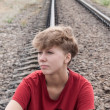 Sad teen girl sitting on rail road - Stock Photo