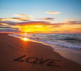 Slovo láska na písčité pláži při západu slunce — Stock fotografie