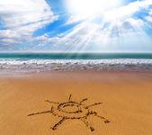 Sun sign drawn on sand of beach — Stock Photo