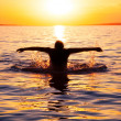 Young man swims in the sea over sunrise — Stockfoto
