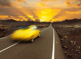 Sunset over fast car and road — Stock Photo