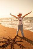 Little girl draws  sun on sand at the beach — Stock Photo