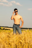 Young man on wheat field — Stock Photo