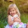 Cute little girl with a bunny rabbit has a easter at green grass — Stock Photo #42165563