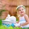 Cute little girl with a bunny rabbit has a easter at green grass — Stock Photo #42166621