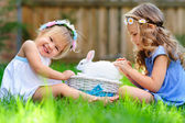 Two little girl with a bunny rabbit has a easter at green grass — Stock Photo