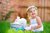 Cute little girl with a bunny rabbit has a easter at green grass — Stock Photo