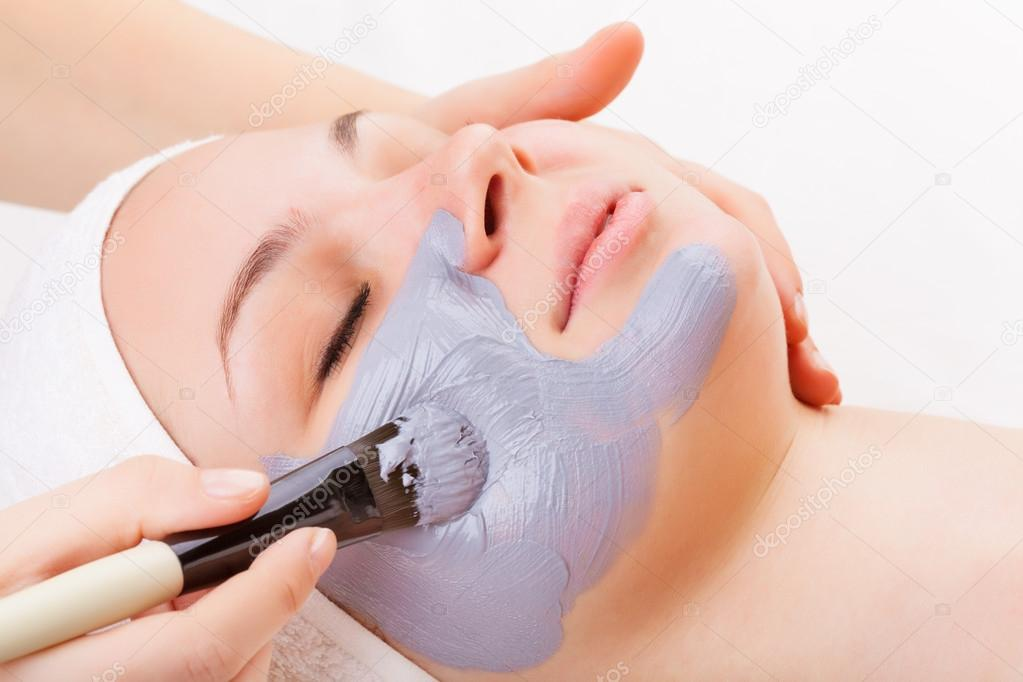 Young woman with clay facial mask on white background — Stock Photo #17460487