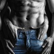 Sexy muscular naked man and female hands unbuckle his jeans — Foto de Stock   #23367332