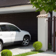 图库照片: White car in front of house