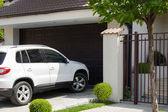 Biały samochód przed domem — Zdjęcie stockowe