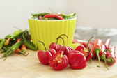 Red and green chilli peppers on a chopping board — Stock Photo