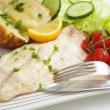 Baked fish fillet, tomatoes, potato and salad - Stock Photo
