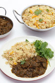 Methi lamb meal with tomato rice and bowls — Stock Photo