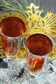 Two glasses in festive tinsel tinsel and mask — Stock Photo