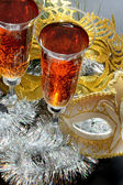 Two glasses in festive tinsel tinsel and masks — Stock Photo