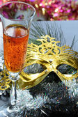 Glasse in festive tinsel tinsel and mask — Stock Photo