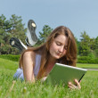 Young girl using a tablet in the park — Stock Photo
