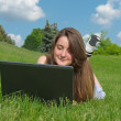 Smiling woman using a laptop outdoors — Stock Photo #12585342