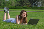 Girl lying on grass with her laptop — Stock Photo