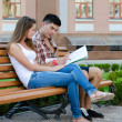 Young couple sitting on a bench reading a map — Stock Photo