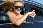 Smiling woman dangling a car key — Stock Photo