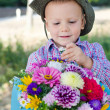 Boy taking a single flower from a bouquet - Stock Photo