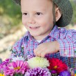 Mischievous little boy with flowers - Stock Photo