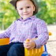 Small boy sitting on a toy truck - Stock Photo