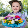 Grinning young boy with flowers - Stock Photo