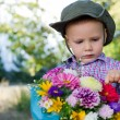Cute little boy with bunch of flowers - Stock Photo
