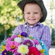Beaming little boy with flowers for his mother — Stock Photo