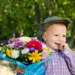 Bashful small boy with a bouquet of flowers - Stock Photo