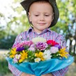 Smiling child presenting flowers — Stock Photo