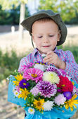 Boy taking a single flower from a bouquet — Stock Photo