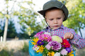Cute little boy with bunch of flowers — Stock Photo