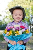 Niño sonriente que presenta flores — Foto de Stock