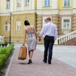 Couple walking with woman carrying luggage — Stock Photo