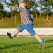 Stock Photo: Little boy midair kicking ball
