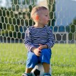 Little boy sitting on a soccer ball — Stock Photo